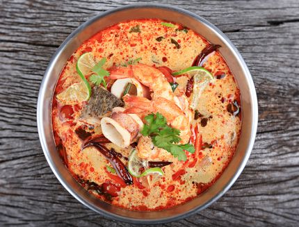 Tom Yum Kung or Tom Yum Goong a Spicy Sour Soup on wooden table top view, Thai local food