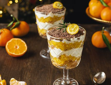 Process of preparation christmas layered dessert, no bake cheesecake or trifle with tangerines and chocolate
