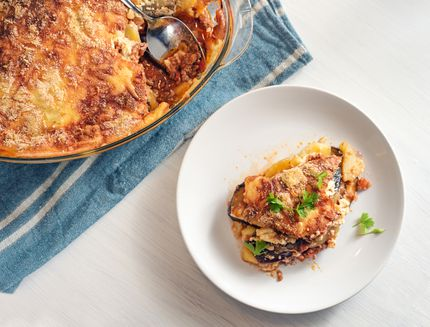 Moussaka baked in a glass casserole and served on a white plate, traditional Greek dish of eggplants, potatoes, minced meat and tomatoes, copy space, high angle view from above