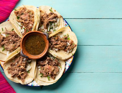 Mexican slow cooked lamb tacos also called barbacoa on turquoise background